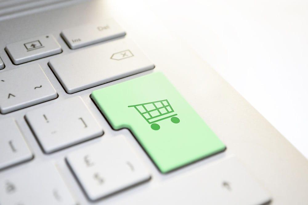 A green enter button of a laptop with shopping cart sticker.