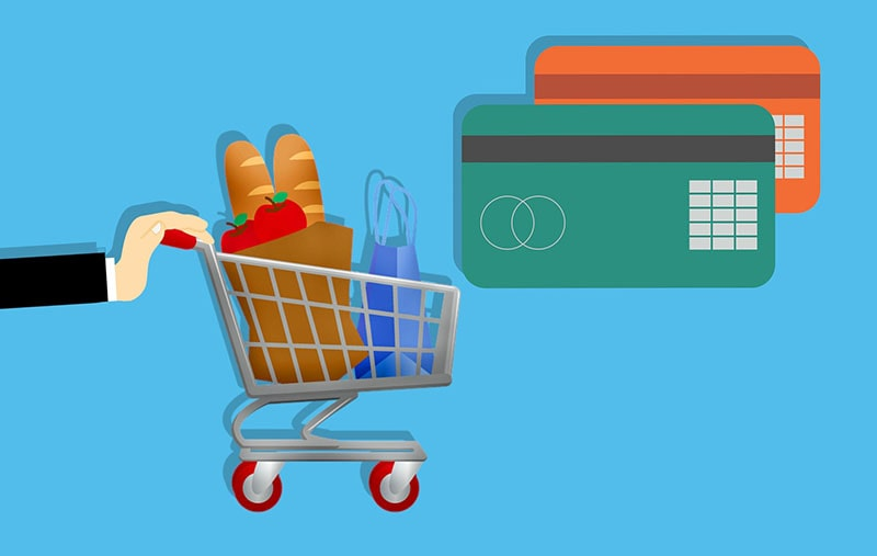 A shopping card with products next to two credit/debit cards.