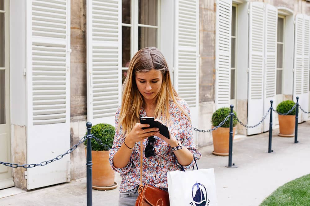 A girl watching her phone while walking.