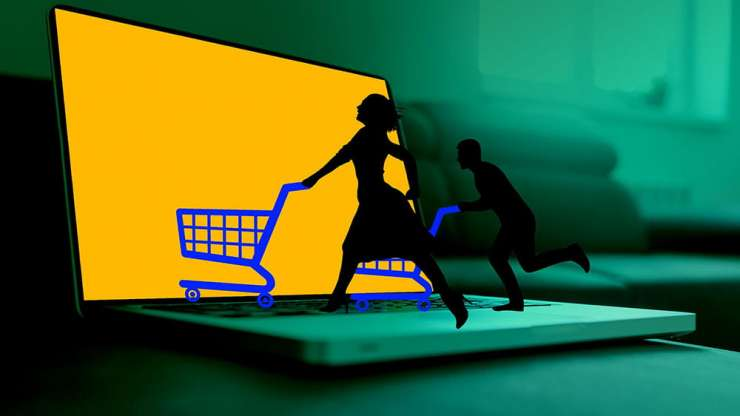 Miniature model people with shopping carts over a laptop.