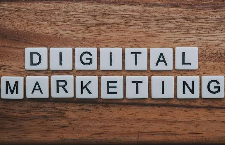 Digital marketing letters from Scrabble on a wooden background.