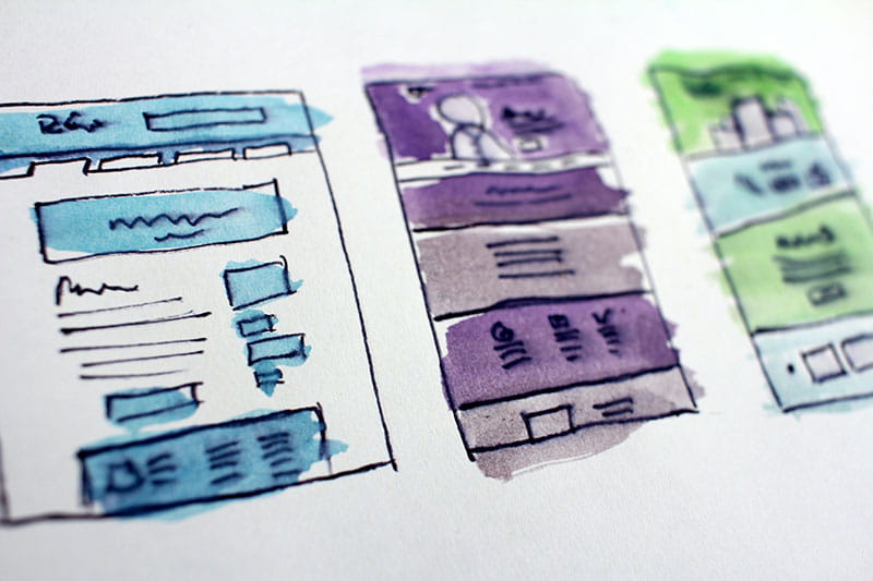 Website designs painted on a white sheet of paper.